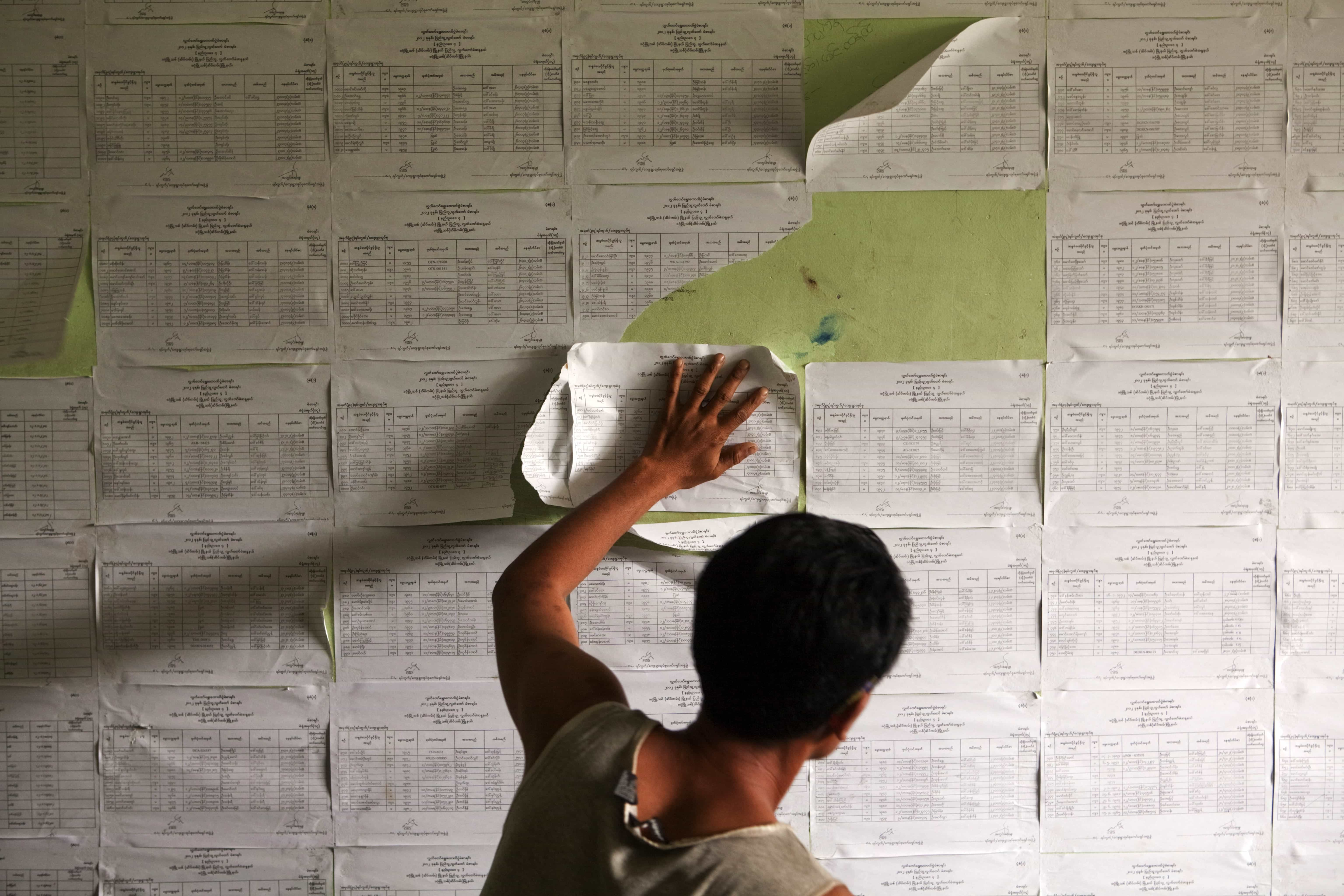 People check their names on the voting register at a polling station in Yangon during the by-elections.