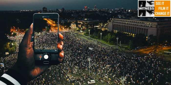 a man holds up a camera phone from a balcony to film protesters in the street at night time