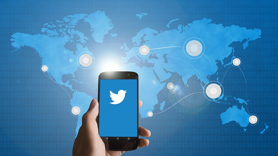 A hand holding a mobile phone with the twitter icon on the phone with a world map as the backdrop