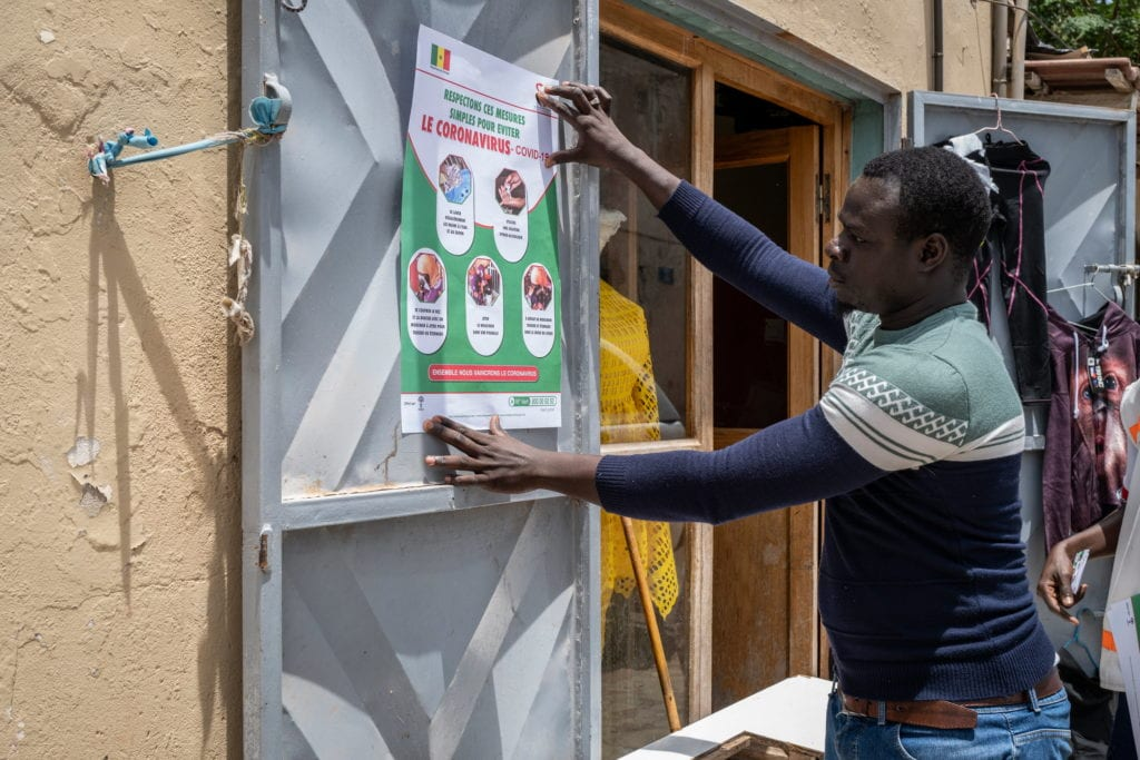 a man pinning up a cornavirus information poster fact sheet on a door in Africa