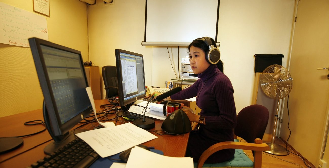 a woman with headphones at a desk on a computer
