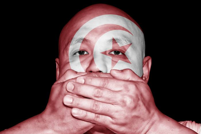 bald man with the tunisian flag painted on his face covers his mouth