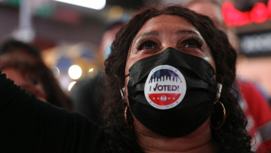 An African-American women wearing a mask with the word 'Voted, raises her face in celebration.