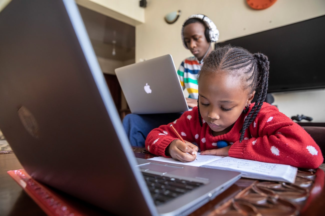 A young girl works with a laptop with her mother sitting behind her