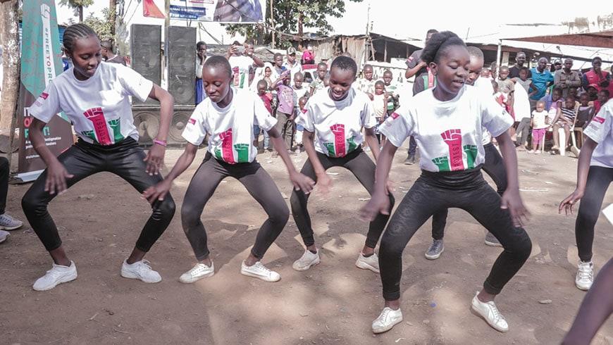 Four girls in Kenya dancing wearing free to protest t shirts