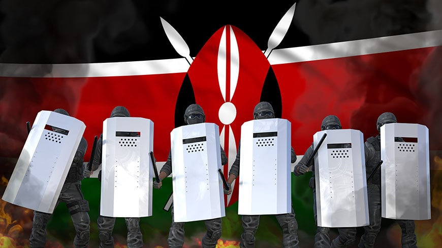 A barricade of police with shields with the Kenyan flag in the background