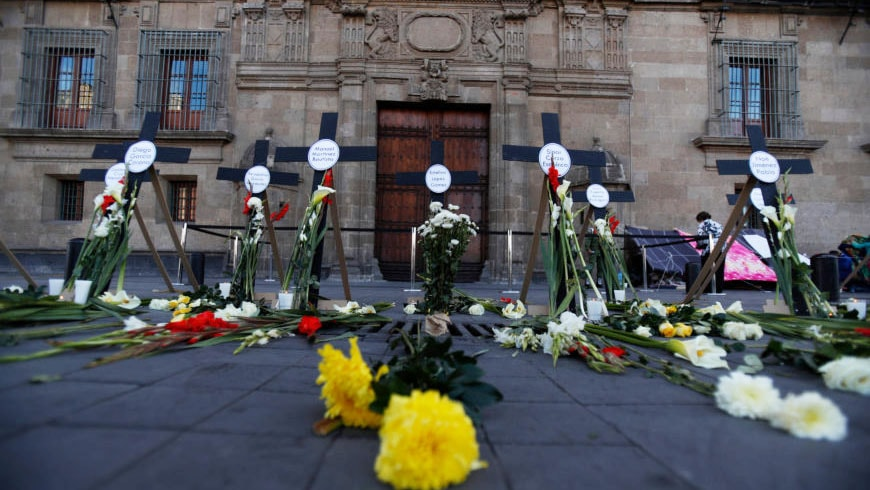 Crosses with the names of 14 murdered journalists and human rights defenders stand in front of the National Palace in Mexico City.