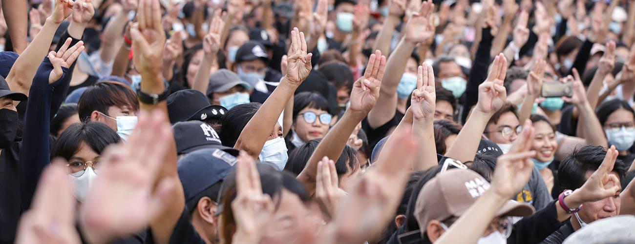 Pro democracy protestors in Thailand raising the three finger gesture