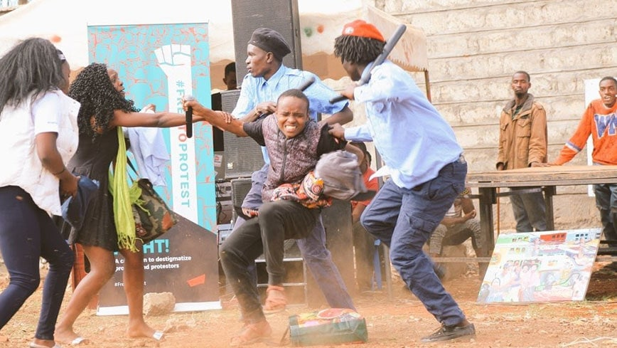 Two policemen detain a student whilst his friend looks on