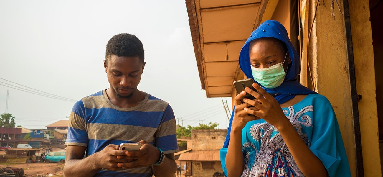 A man and a woman in Africa one wearing a face mask look at their phones