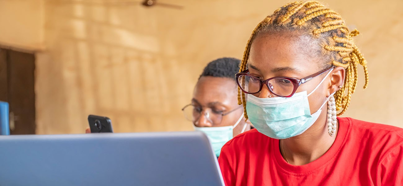 An African woman wearing a Covid-19 mask works on a laptop, in the background a man looks on his mobile