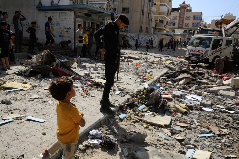 Young child and older man inspect damage caused by an Israeli air strike.