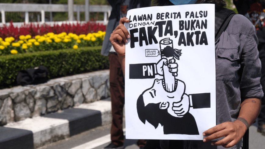 A poster reading 'Fight fake news with facts, not acts'