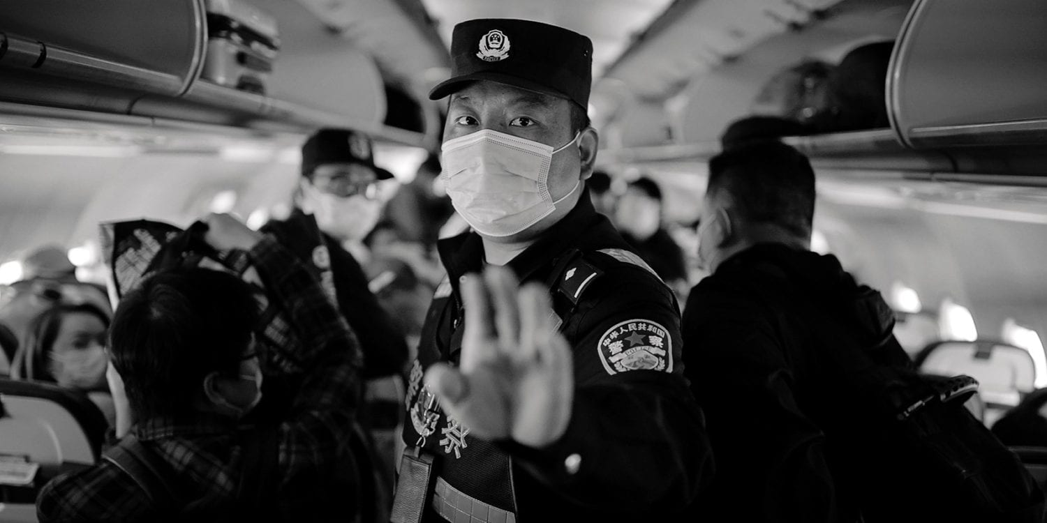 A policeman orders Reuters journalists off an airplane without explanation while the plane is parked on the tarmac at Urumqi airport, Xinjiang Uyghur Autonomous Region, China, 5 May 2021.